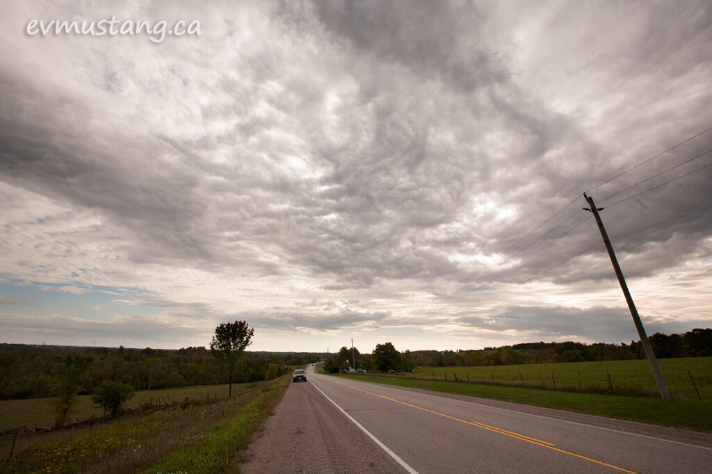image of a two lane highway stretching into the distance along a cow pasture under a dramatic grey cloud