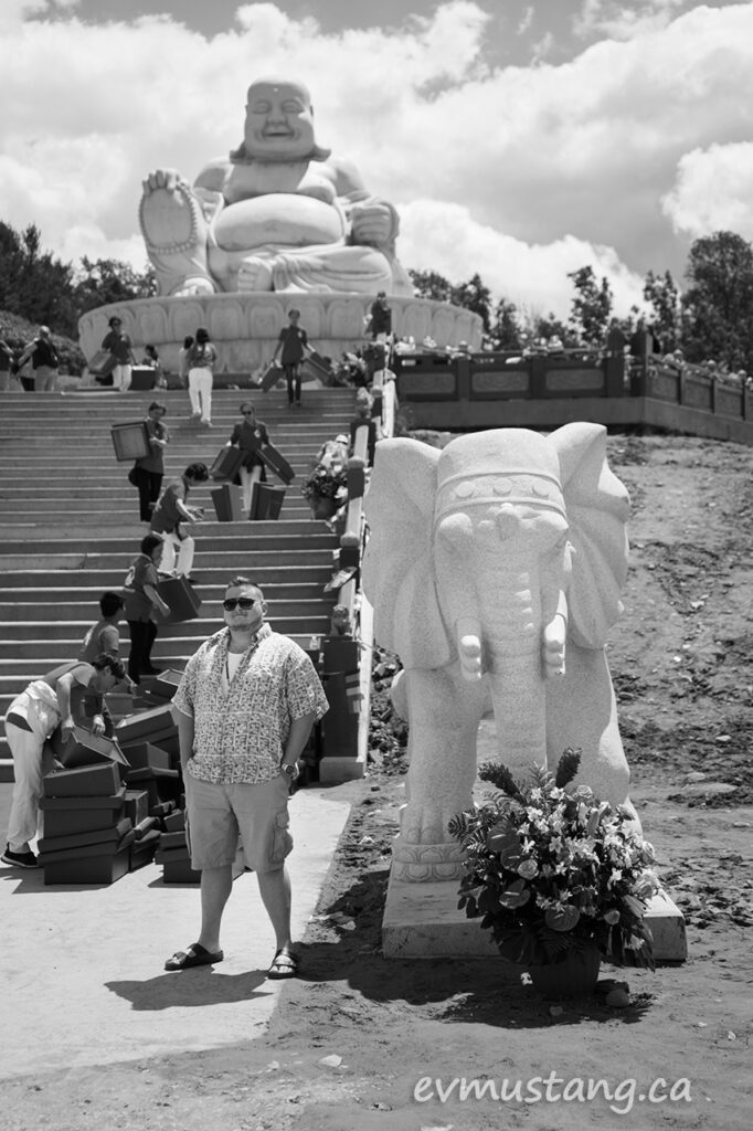 image of a large male tourist standing at the foot of the new buddha sculpture at the cham chan temple outside peterborough ontario