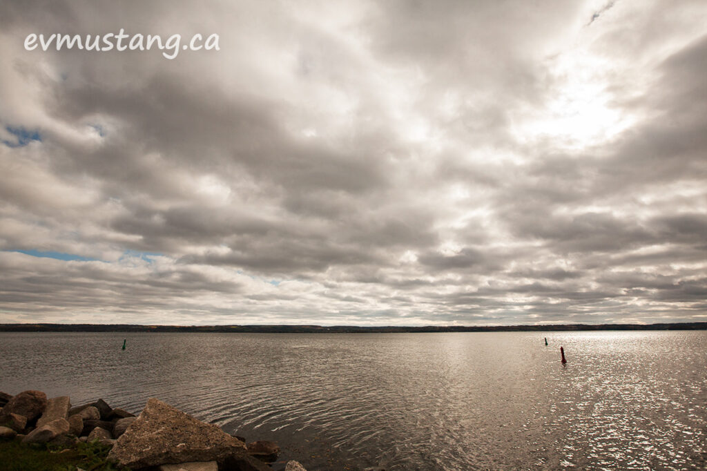 image of buoys in rice lake with a patch of sun breaking through the clouds creating reflections on the water with one large shore rock in the foreground