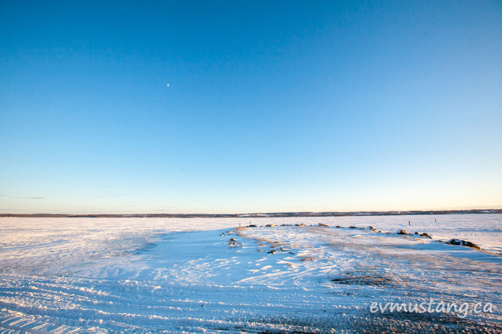 image of half moon in a crystal blue sky above a barren lake of ice and rock