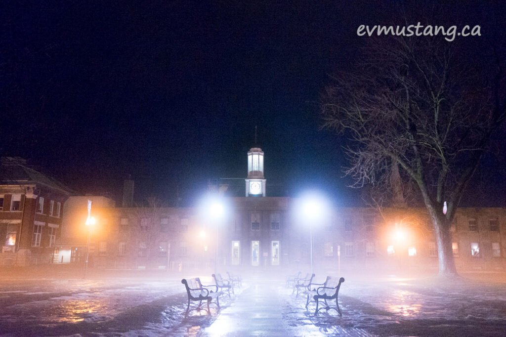 image of peterborough city hall in fog at night with park benches stretching out in front toward the camera
