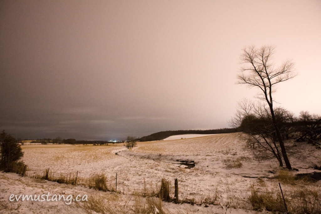 image of a wide rolling country hillside with snow at night