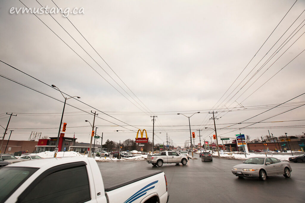 image of the intersection of lansdowne and the parkway in peterborough, ontario on a cloudy day three days before christmas showing turning cars and trucks on wet pavement