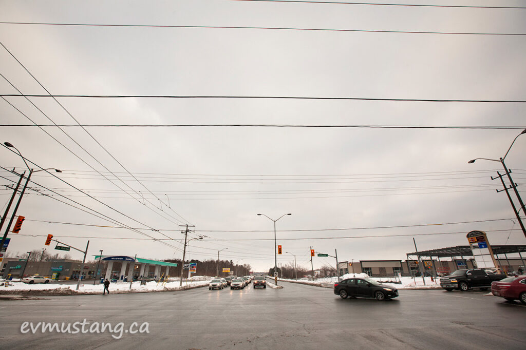 image of the intersection of lansdowne and the parkway in peterborough, ontario on a cloudy day three days before christmas showing stopped taffic at the lights waiting to drive toward the viewer with one car turning left