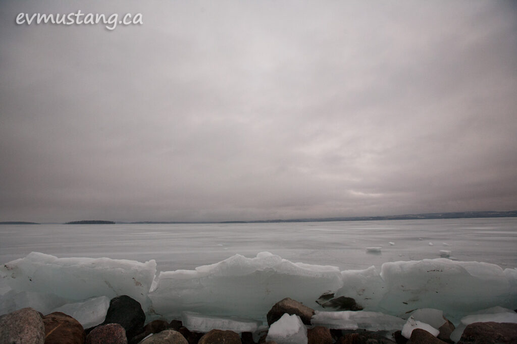 image of ice and rocks on rice lake under sun warmed cloud cover