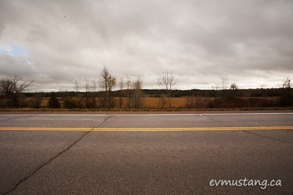 image of dark november sky over two lane county road which splits the frame with the yellow dividing line at the two thirds level
