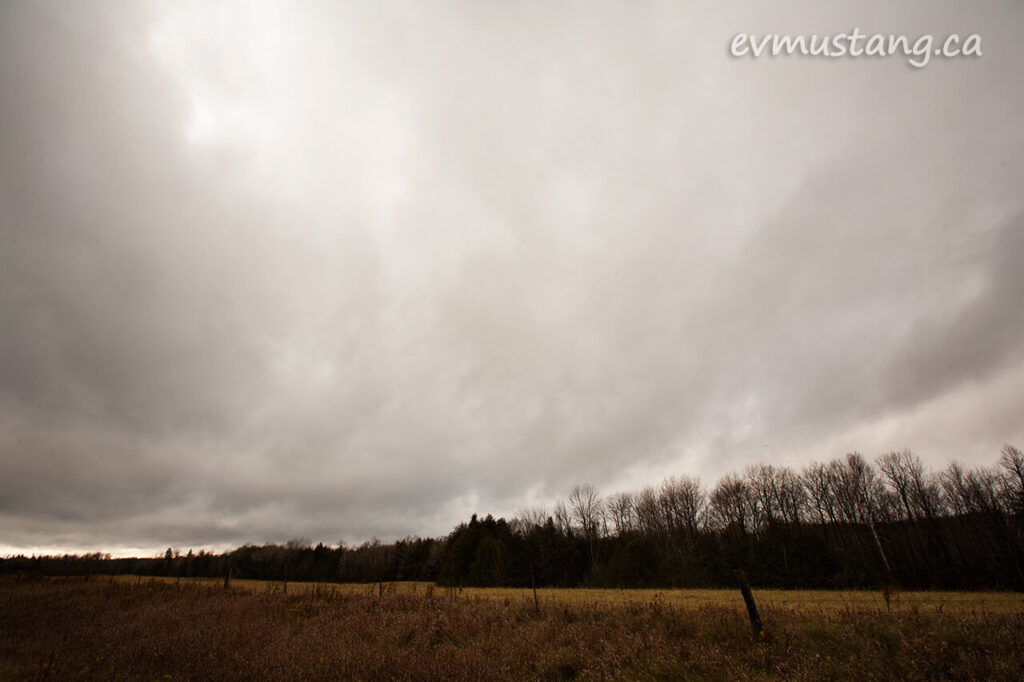 image of dark november sky over fallow field and trees
