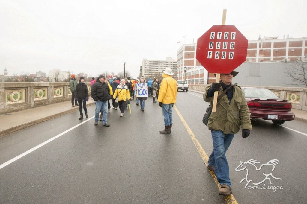 image of protesters taking over the hunter street bridge in peterborough ontario for the may 1st general strike against ford